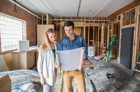 un homme et une femme regardant des plans dans une maison en construction